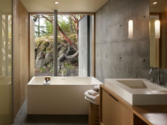 bathroom-interior-design-with-concrete-walls-and-square-shaped-bathtub-with-glass-window-transparent